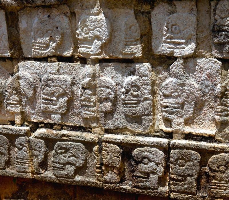 stone wall of skull heads at chichen itza