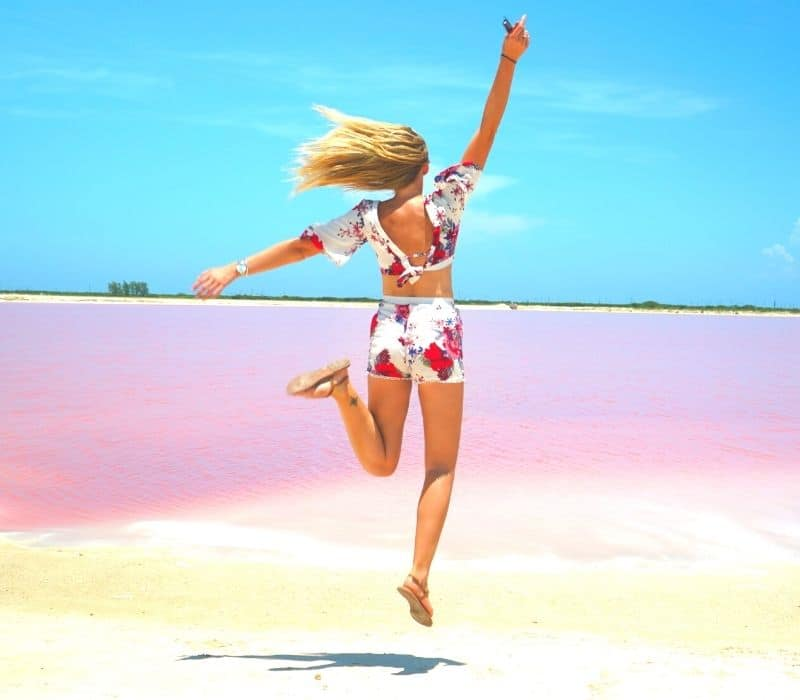woman jumping at the pink lakes in mexico