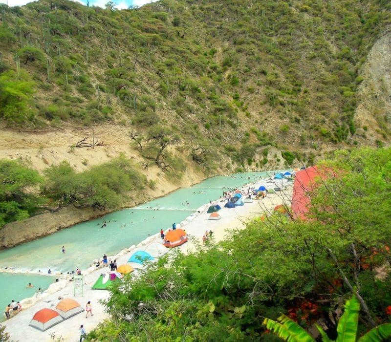 tents set up by a river - Visit Las Grutas Tolantongo