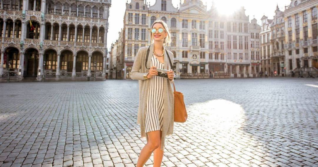 Woman standing in a city square with her camera