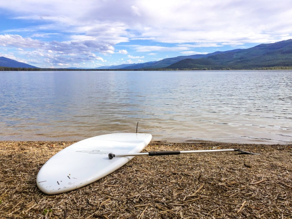 Swan Lake, Montana: stand up paddle board next to lake on beach with mountains in background.