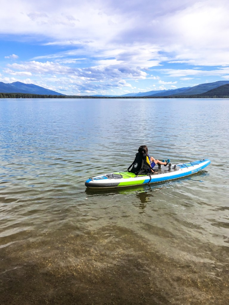 My daughter hanging out on a paddle board near the public day use beach area of Swan Lake, Montana.
