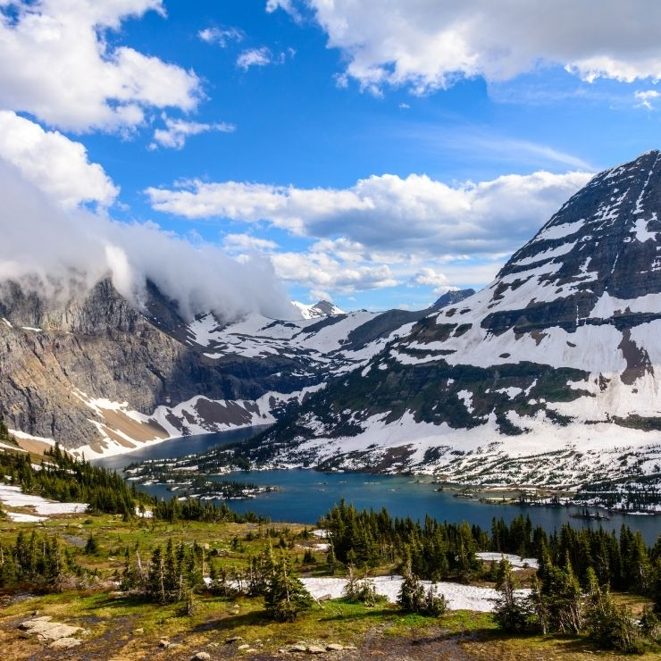 Snowcapped peaks above a peaceful lake in Glacier National Park