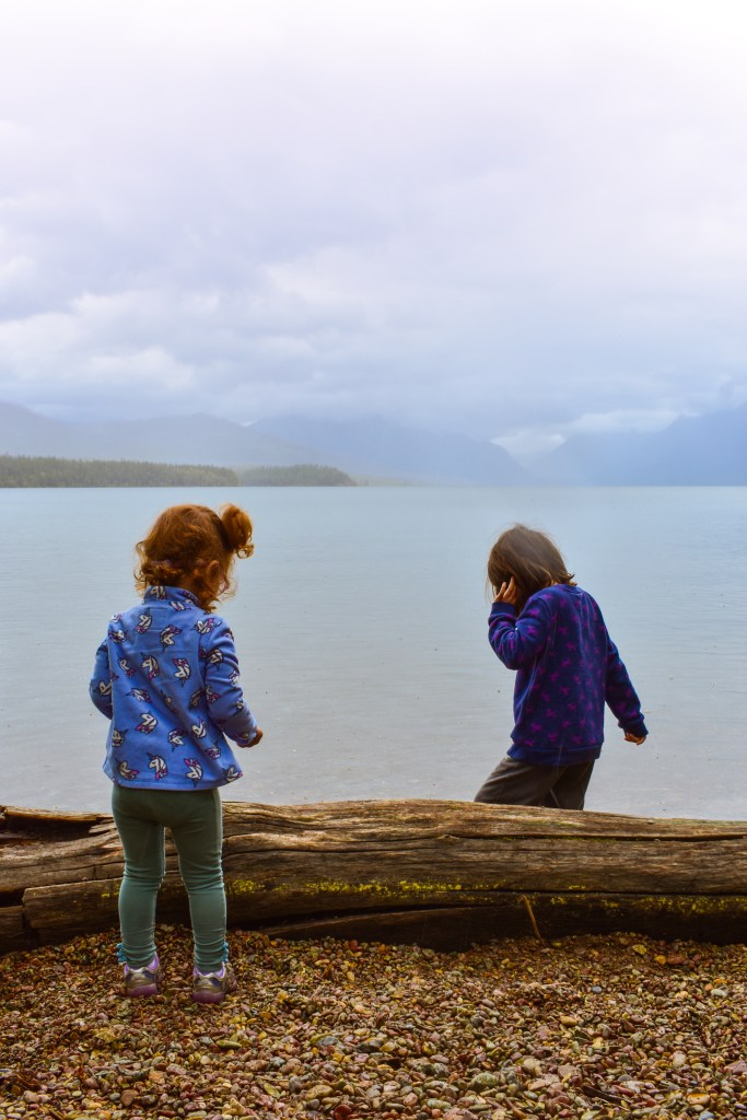 Kids playing on the shores of Lake McDonald in Glacier National Park.