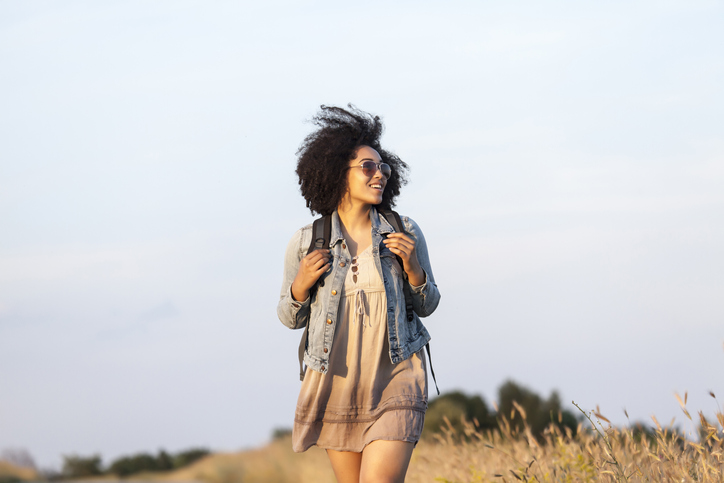 Carefree african woman walking on empty country road, enjoying the sun.
