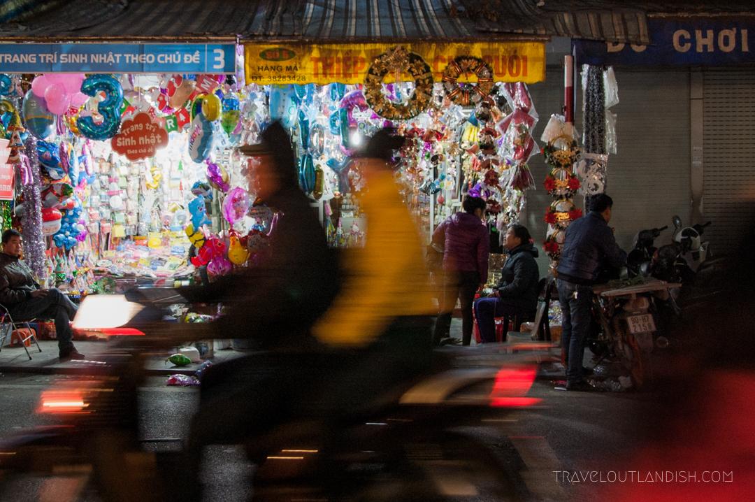 A Couple Riding a Motorbike through a Night Market