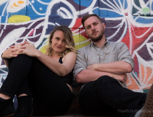 Daniel and Taylor sitting in front of a mural in San Francisco
