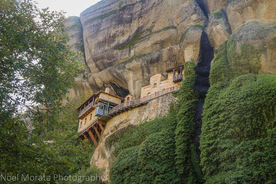 A monastery tucked into a cliff with a seasonal waterfall to the right