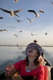 Ana is delighted to watch the seagulls circle overhead while we fed them on Inle Lake, Burma (Myanmar).