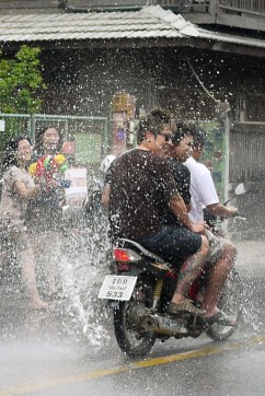 A motorbike getting nailed with water for Songkran in Chiang Mai, Thailand