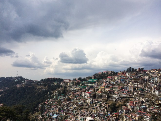 Dark clouds gather over the cluster of buildings in Shimla