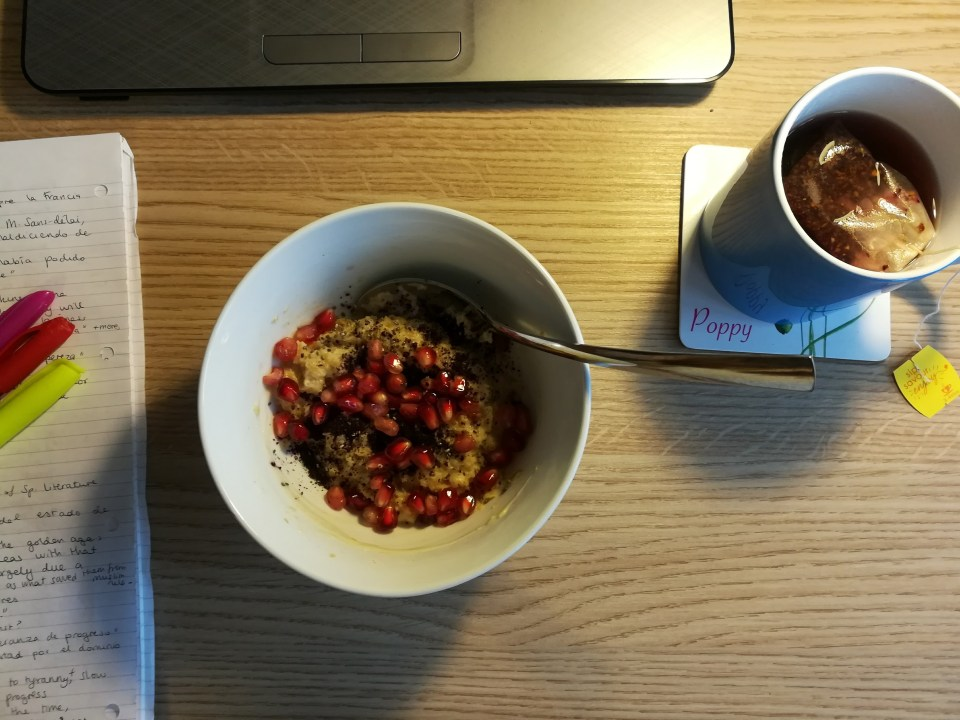 A bowl of porridge with pomegranate seeds and chia seeds next to a mug of fruit tea, viewed from above.