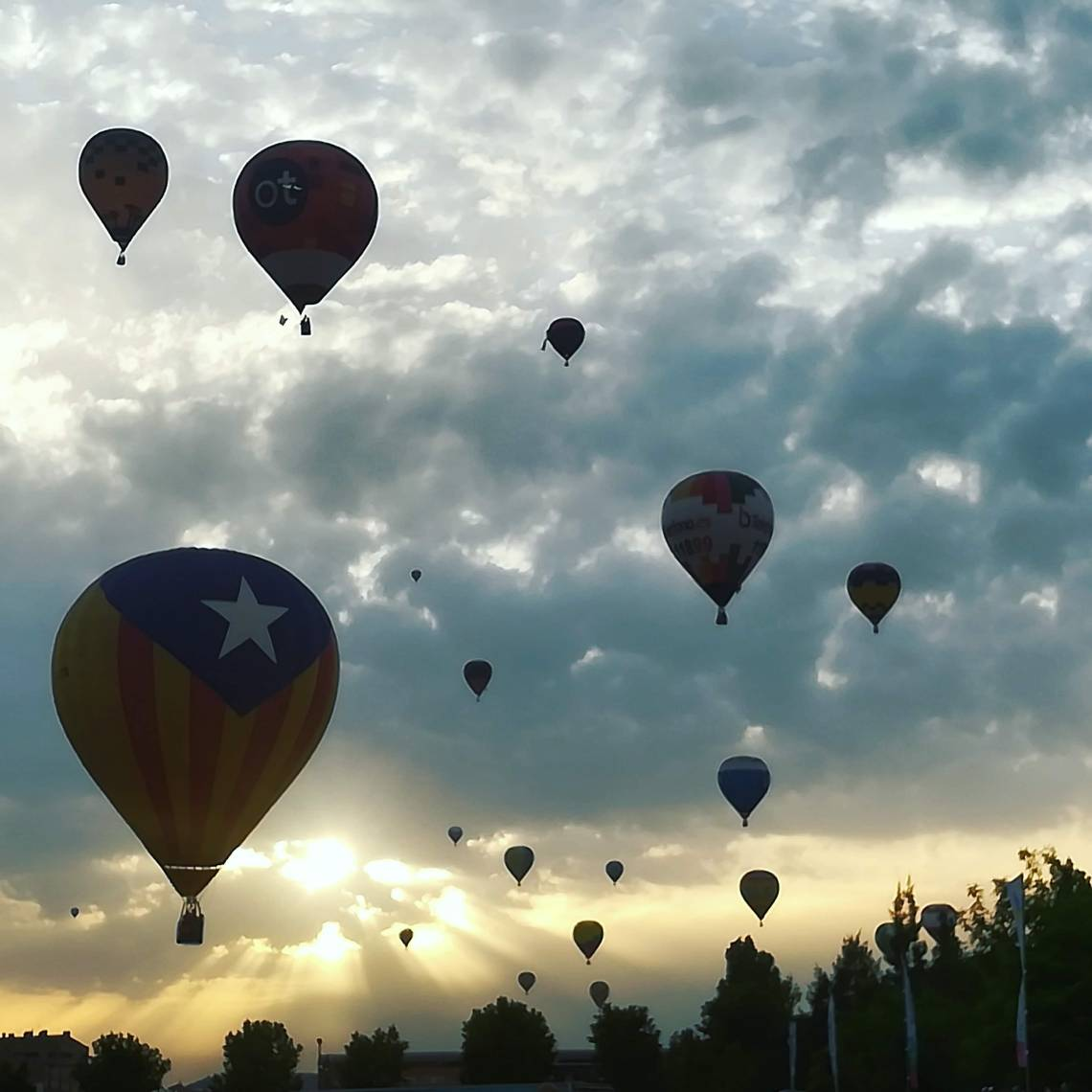 The European Balloon Festival. Shot of the sky from below, with many balloons silhouetted in the background. The foreground shows a balloon with the Catalan flag.
