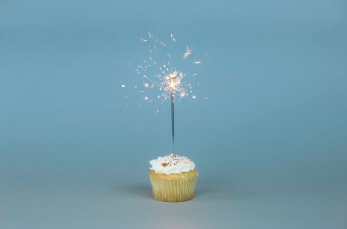 A cupcake with a sparkling candle on a blue background