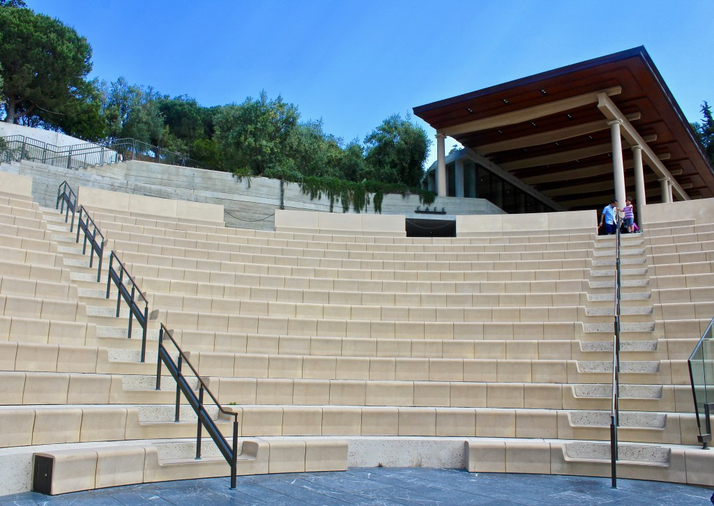 Getty Villa includes an amphitheater which hosts performances and an annual Greek play. At the top of the photo is the cafe, designed to look like the temporary roof over an archeological dig. (Photo by Suzanne Ball. All rights reserved.)