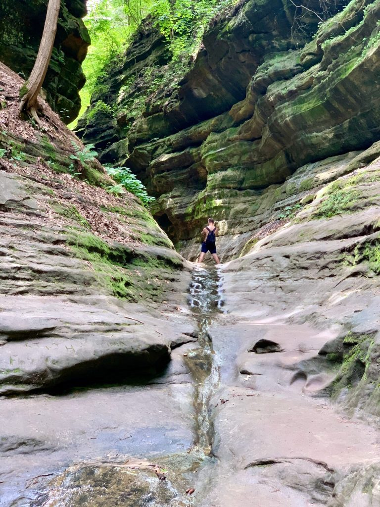 A hiker at the bottom of one of the sandstone canyons at Starved Rock State Park.