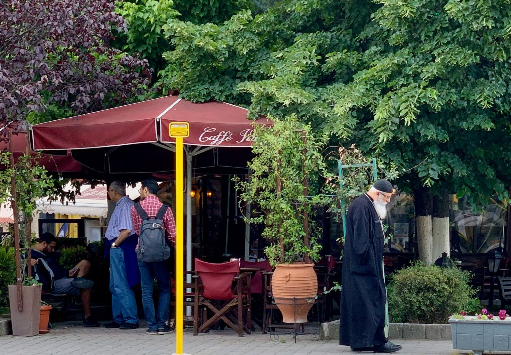 A priest walks by as tourists stop to look at a restaurant menu. There are plenty of things to do in Meteora Greece.