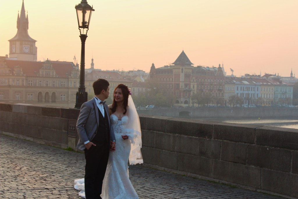 A bride and groom stop for a photo op in Prague's morning light.