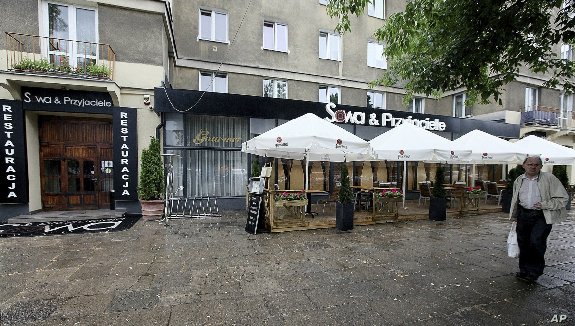 FILE - A man walks in front of the now-closed restaurant Sowa & Przyjaciele, June 20, 2014 , where top Polish politicians and business people were secretly and illegally recorded over hundreds of hours in 2013 and 2014, in Warsaw, Poland.
