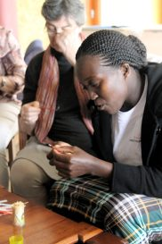 The women from Dorcus beads teach members of the Kenya Embroiderer's Guild how to make recycled beads