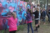 Frida, Lottie and Leon add to the graffiti wall at Urkult 2019