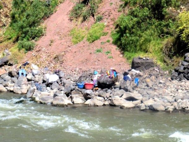 Washing clothes by river in Peru