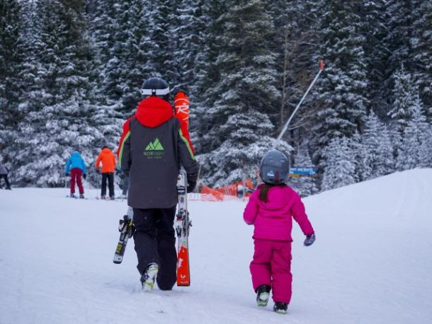 Ski instructor carrying kids skis and her own with young girl