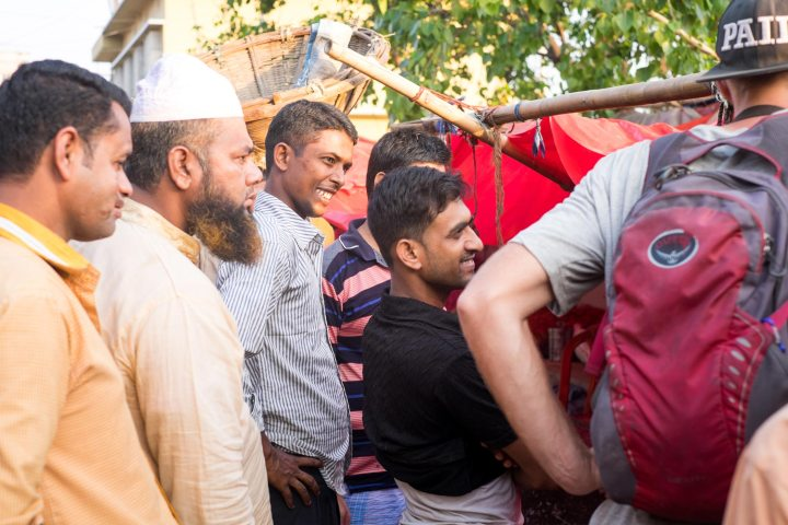 A crowd of locals asks a tourist questions in a market in Bangladesh.