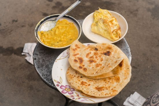 Paratha, dal and omelette on a table in Barisal, Bangladesh.