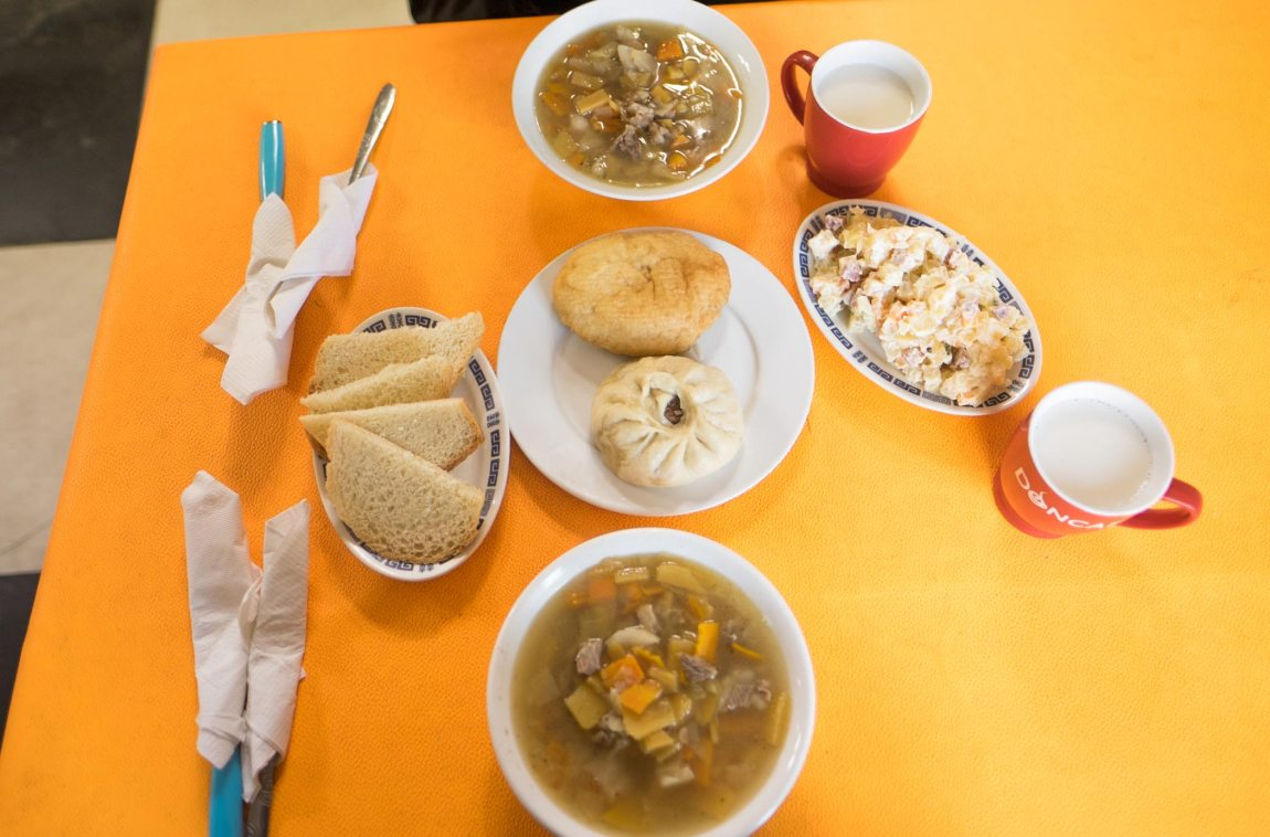 A table of mutton soup, dumplings and Russian salad in Mongolia.