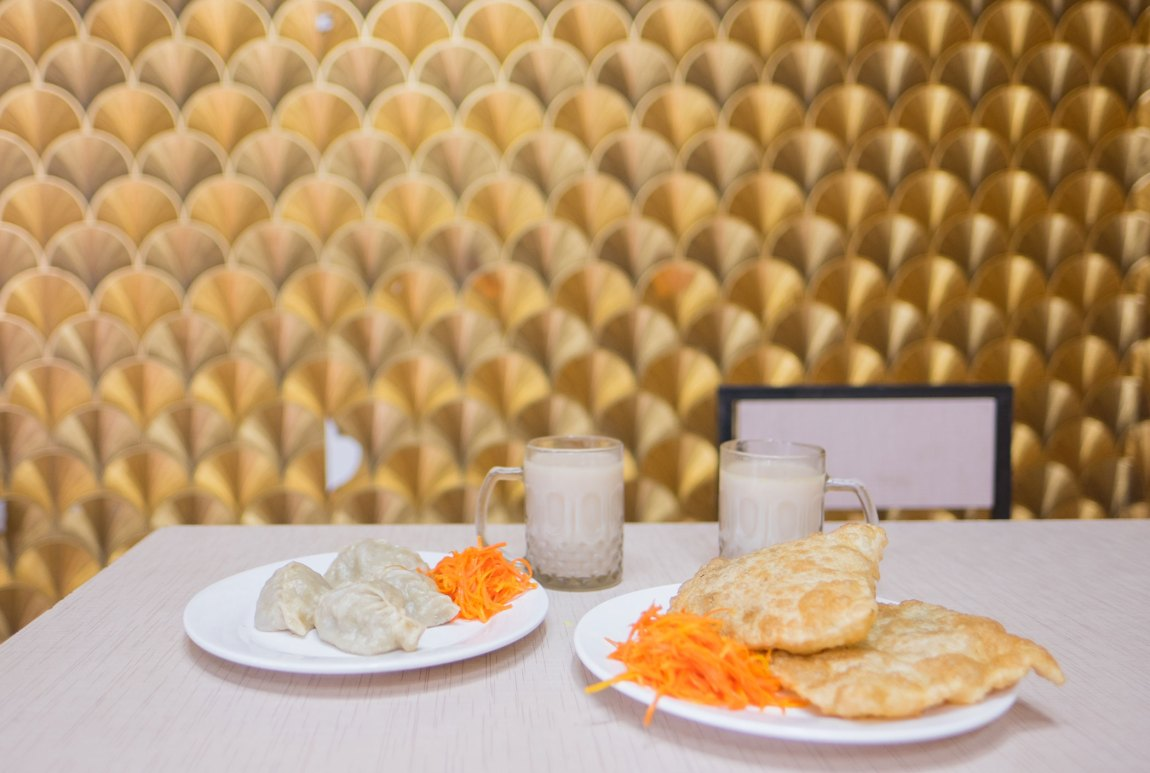 Buuz, khuushuur and suutei tsai on a table in Mongolia.