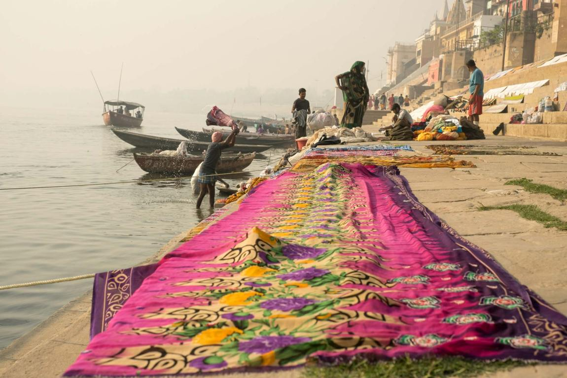 People doing laundry in Varanasi and a colourful piece of material