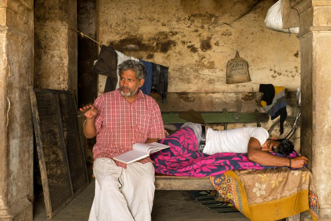 A man talks and a man sleeps in the cow house in Varanasi