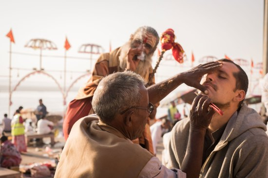 A man gets shaved on the ghat in Varanasi.