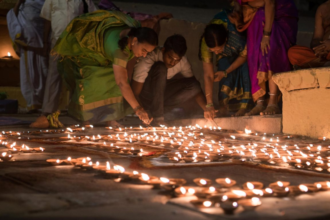 People light candles on the banks of the river Ganges.