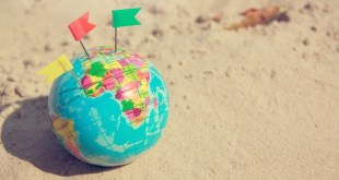 Travel summer Concept With Earth Map Ball on saNd