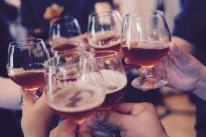 mani che reggono un bicchiere di birra in un brindisi