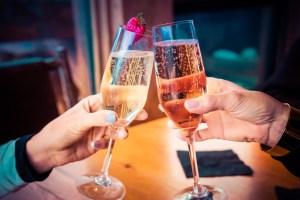 due mani reggono due calici di champagne