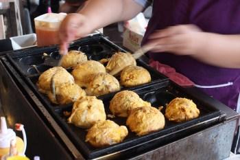 cuoco asiatico che prepara i takoyaki con le bacchette
