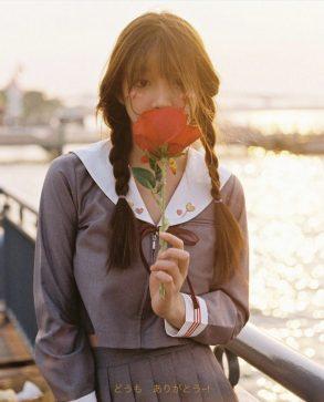 ragazza giapponese con divisa alla marinara e con fiore rosso in mano pasto giapponese il mio viaggio in giappone traveltherapists miglior blog di viaggio