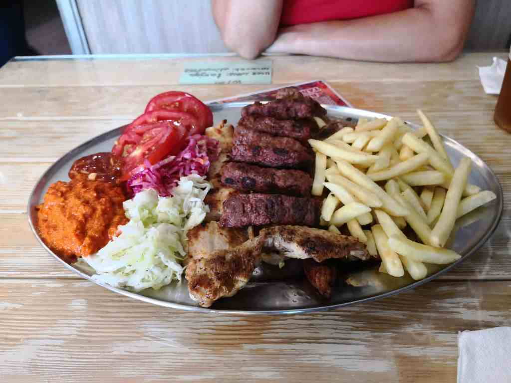 a mixed meat platter with fries, tomato, lettuce and ajvar