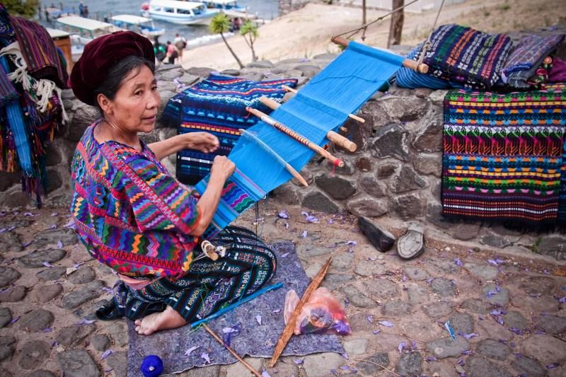 Guatemalan indigenous woman weaving traditional crafts on the lake Atitlan
