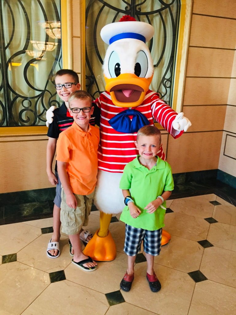 Photo of Kids with Donald Duck on Disney Cruise | Disney Cruise Fare: What's Included and Things You Should Know For Your First Disney Cruise by popular family travel blog, Travel with a Plan: image of three boys standing with Donald Duck.