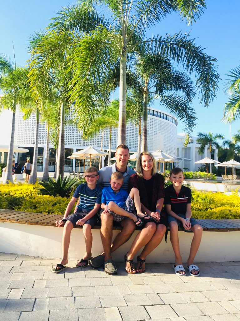 Our family sitting on a bench near the lobby as part of our Ocean Riviera Paradise review