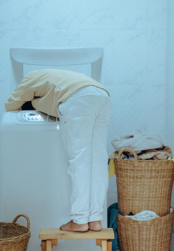 woman leaning into a washer cleaning a sturdibag pet carrier
