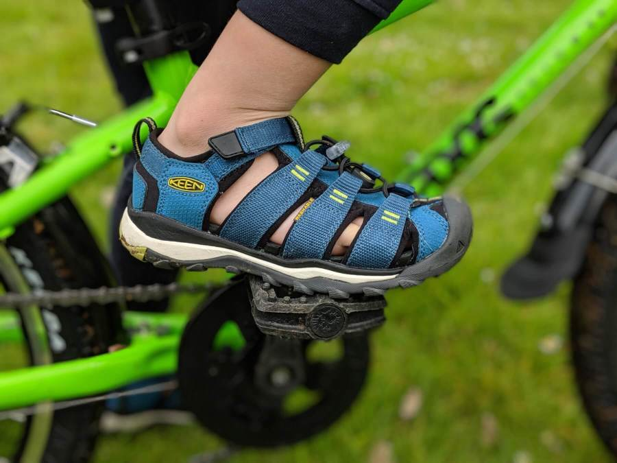 kids blue sandal on pedal of bike