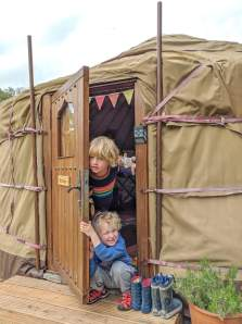 boys coming out of yurt door