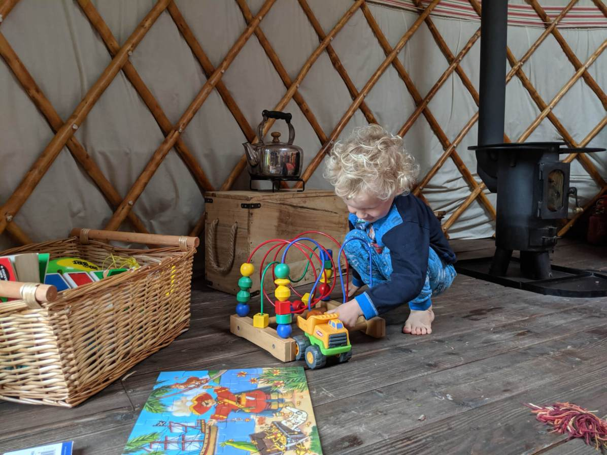 boy playing with toys in yurt
