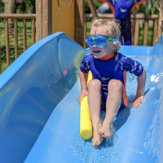 young boy on water slide