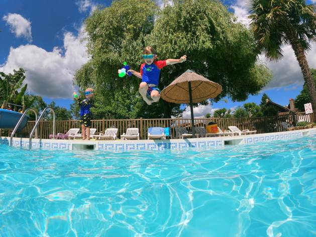 boy jumping in to swimming pool